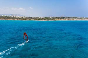 Aerial shot of a man windsurfing in the Aegean Sea, with the coast of Paros in the background