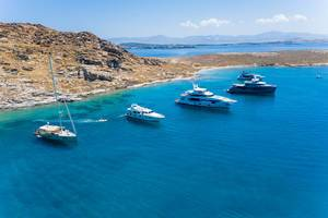 Aerial shot of expensive, luxury boats on the Mediterranean Sea, in a bay between Tourkou Ammos beach and Monastiri Beach, in front of the island Paros, Greece