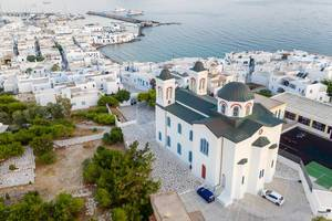 Aerial shot of the colorful limestone main church and fishing port in Naoussa on Paros Island (Greece)
