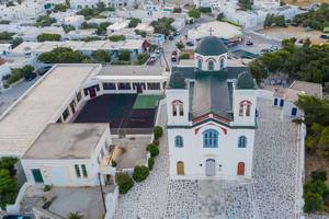 Aerial shot of the colourful main church of the beautiful port city Naoussa on Paros, Greece