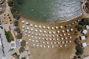 Aerial shot of white parasols, lined up on a sandy beach at the Aegean Sea at Paros, Greece