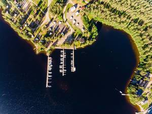 Aerial shot shows yachts and motorboats dock at wooden jetties on Päijänne lake at Padasjoki