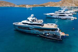 Aerial vie of People on vacation on a multi-storey yacht ship, with a Marvel 41 Passenger Armored rib boat, in a bay near Naoussa, Greece
