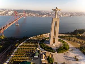 Aerial view drone shot from behind of the Cristo Rei monument with Ponte 25 de abril bridge in Almada Lisbon