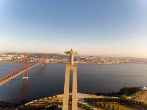 Aerial view from behind of the Cristo rei monument with ponte 25 de abril bridge in Almada Lisbon