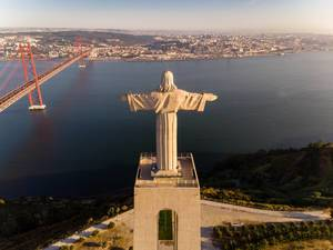 Aerial view from behind of the Cristo Rei statue in Almada, looking over the Tajo river with Ponte 25 de Abril bridge