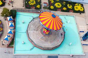 Aerial view of a chairoplane swing carousel with circus colors in a pool at Lake Michigan