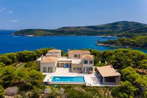 Aerial view of a greek villa with private pool, with view of the blue sea and Paralia Zogeria Beach
