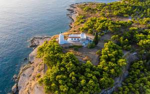 Aerial view of a lighthouse on the remote part of the island Spetses, Greece, next to the rocky coast and the blue ocean