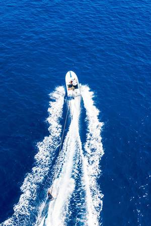 Aerial view of a sporty man water-skiing on the blue Myrtoan Sea