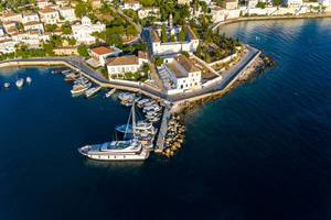 Aerial view of an anchored luxury yacht and fisher boats in the old harbour of the Argosaronic island Spetses, Greece, in front of church Agios Nikolaos