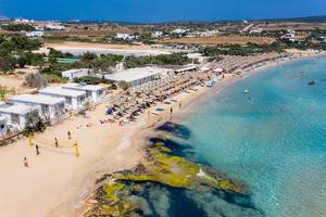 Aerial view of holidaymakers playing beach volleyball and relaxing at Santa Maria Beach, Paros, at the coast of Aegean Sea