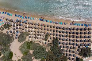 Aerial view of lined up bast parasols on the white sandy beach Santa Maria on Paros, Greece, at the turquoise Mediterranean Sea