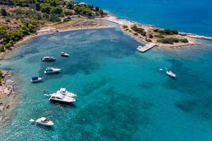Aerial view of motor boats in a blue bay at Hinitsa Beach in Porto Cheli, Greece