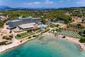 Aerial view of the modern beach hotel Aks Hinitsa Bay and holiday guests in the green sea in front of Chinitsa, Greece