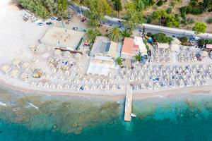 Aerial view of the popular Κaiki Beach with people playing Beachvolleyball, on Spetses, Greece