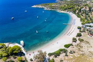 Aerial view of the sea in several blue shades and vacationers on boats in the holiday region Agii Anargiri on Spetses