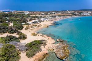 Aerial view of tourists on vacation at the Santa Maria Beach with beach bar and swimming people in the Mediterranean Sea in front of the Greek island Paros