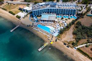 Aerial view shows the luxurious beach hotel Nikki Beach Resort & Spa, with rooftop bar, private swimming pool and direct access to the green sea