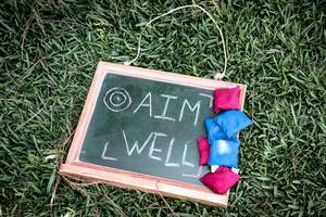 AIM WELL written on a chalkboard with tossing bags on the side
