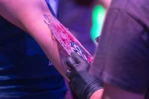 Airbrush-Tattoo am Messestand von Blizzard. Gamescom 2018