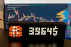 Aktueller Bitcoin Kurs, angezeigt mit der Lametric Uhr, vor einem verschwommenen PC-Bildschirm