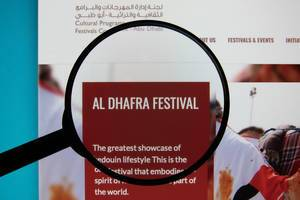 Al Dhafra Festival website on a computer screen with a magnifying glass