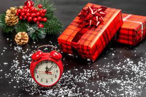 Alarm clock and red decorated gift boxes on a black background with snow and Christmas tree branches (Flip 2019)