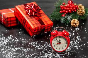 Alarm clock and red decorated gift boxes on a black background with snow and Christmas tree branches