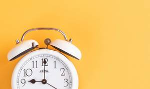 Alarm clock on yellow background with empty space
