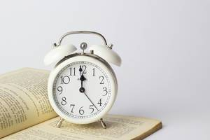 Alarm Clock showing almost midnight and standing on an open book on white background