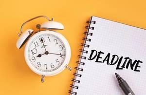 Alarm clock with handwritten Deadline text on yellow background
