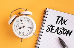 Alarm clock with handwritten Tax Season text on yellow background