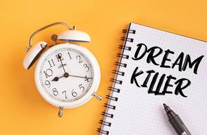 Alarm clock with handwritten text Dream Killer on yellow background