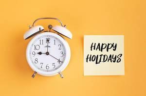 Alarm clock with handwritten text Happy Holidays