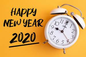 Alarm clock with handwritten text Happy New Year 2020 on yellow background