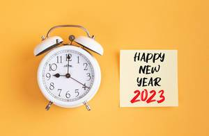 Alarm clock with handwritten text Happy New Year 2023