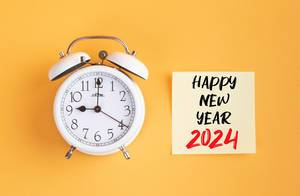 Alarm clock with handwritten text Happy New Year 2024