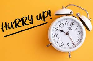 Alarm clock with handwritten text Hurry Up on yellow background