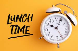 Alarm clock with handwritten text Lunch TIme on yellow background