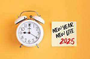 Alarm clock with handwritten text New Year New Life 2025