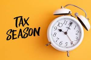 Alarm clock with handwritten text Tax Season on yellow background