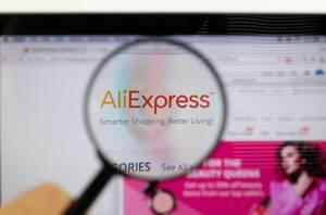 AliExpress-Logo am PC-Monitor, durch eine Lupe fotografiert