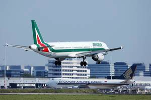 Alitalia plane landing at Amsterdam Airport, Singapore Airlines Cargo at terminal