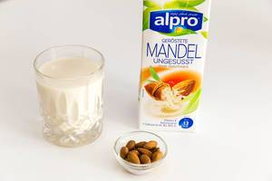 Almond milk by Belgium manufacturer Alpro, unsweetened, next to a glass of vegan milk and a small bowl with whole nuts