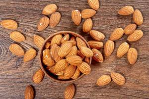 Almond nuts in wooden bowl on brown wooden background. Top view (Flip 2019)