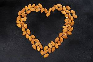 Almond nuts on a black background lined in the shape of a heart. Top view (Flip 2019)