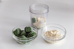 Almond protein powder and frozen spinach in glass bowls and mixer vessel, as ingredients for a high-energy smoothie
