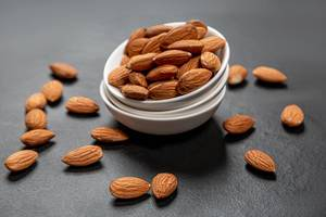 Almonds in white ceramic bowl on black background