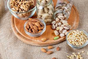 Almonds, pistachios, pine nuts and walnuts on a wooden kitchen board with burlap (Flip 2020)